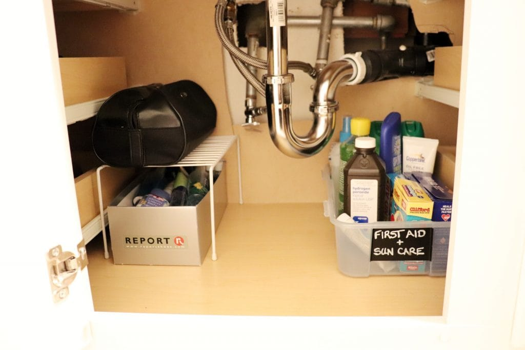 a shot showing under a bathroom sink with a plastic container holding first aid supplies and sunscreen, the under sink pipes, and on the other side, a grey shoe box stacked under a black toiletries bag