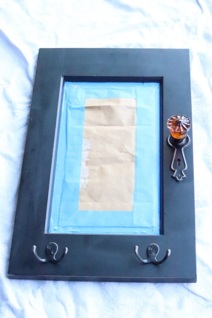 a black framed mirror lying on a canvas background with the mirror part masked with blue painter tape and paper