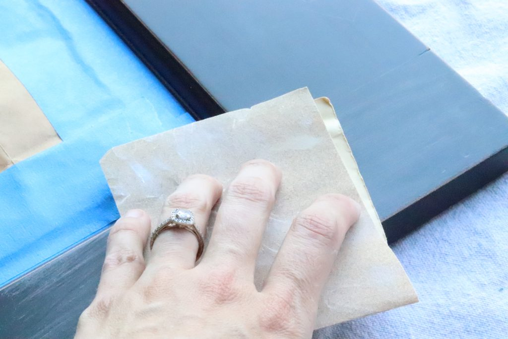 A hand with a ring on it holding sandpaper and sanding down a black wood frame against a canvas background, with blue painter's tape on the left hand side