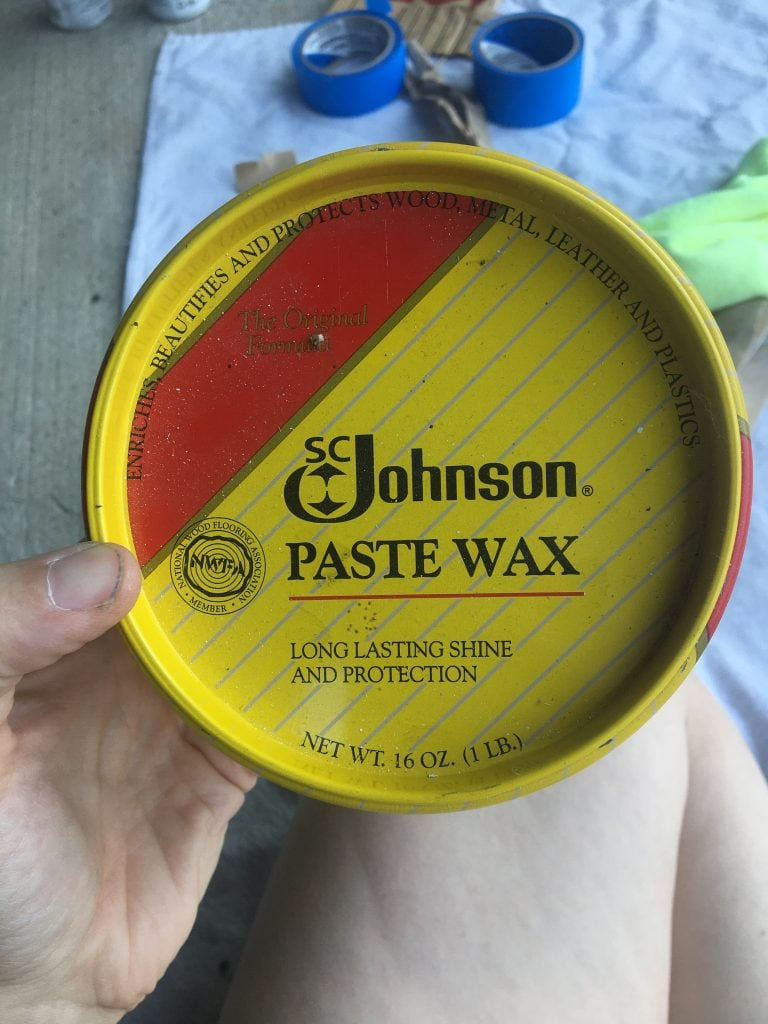 Close-up of a yellow and red paste wax container with blue painter's tape in the background
