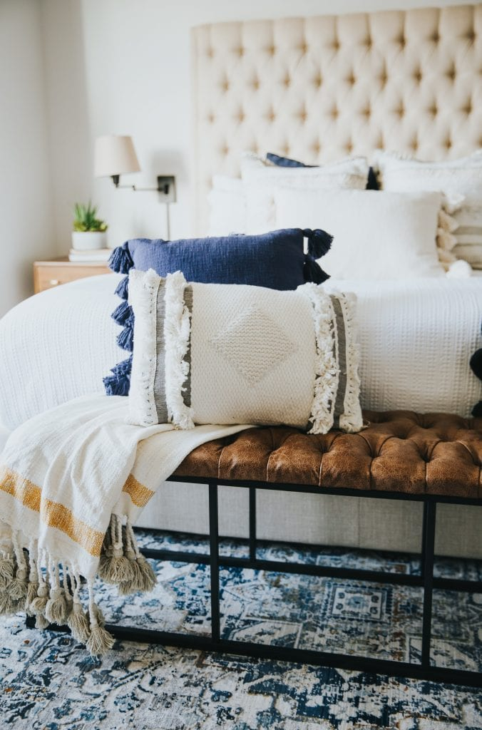 Throw pillows sitting on a leather upholstered bench at the end of a bed with a ivory tufted headboard