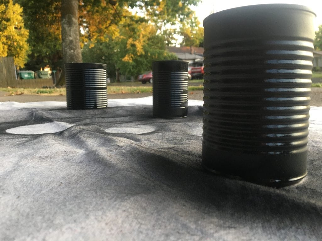 Three tin cans painted black sitting a drop cloth with trees and a car in the background