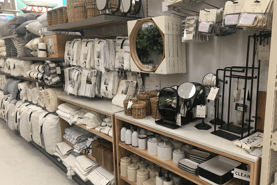 A wall display at a home decor store featuring lots of mirrors, bed linens, bathroom accessories and more