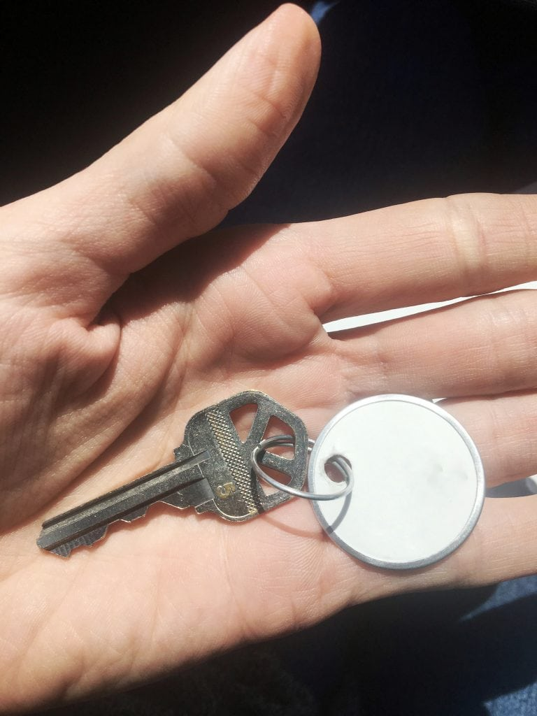 a key with a blank white tag sitting in the open palm of a hand