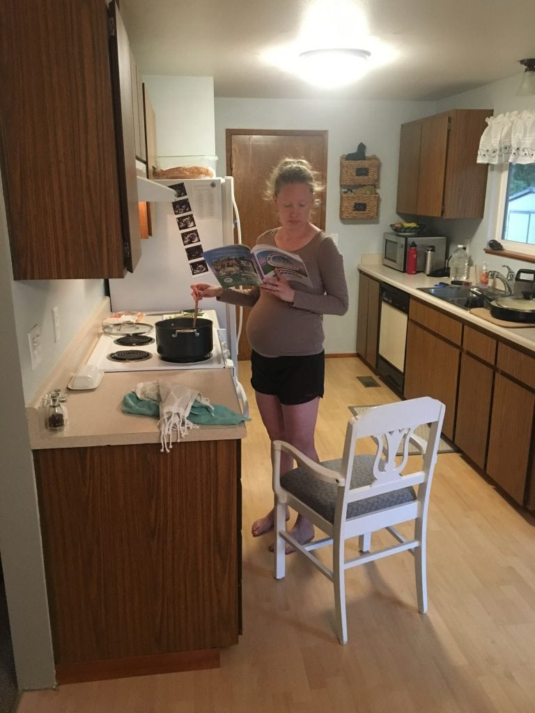 Blonde pregnant woman standing at a stove in a kitchen stirring a pot