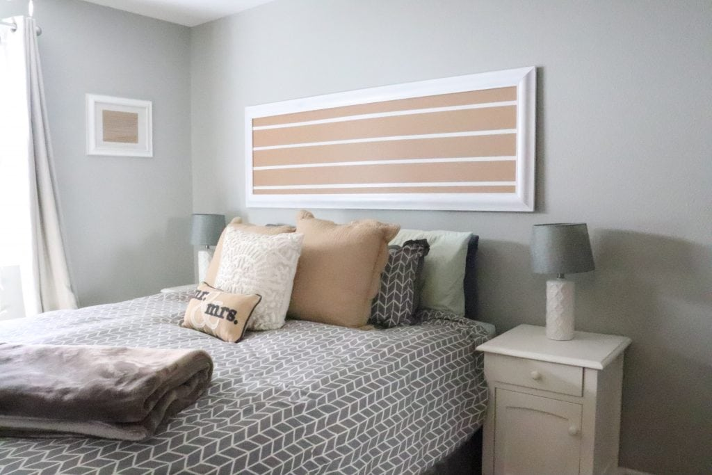 A made queen bed with throw pillows on it, a white nightstand with a white lamp and grey lamp stand on it in a grey room with a tan headboard with white stripes on it