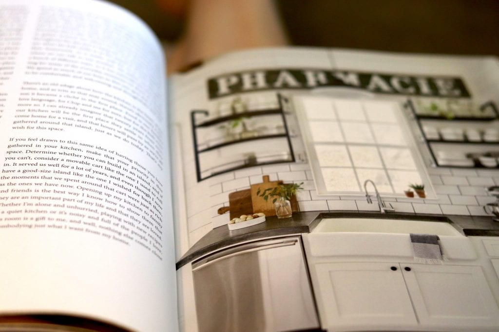 Open book with words on one page and a picture of a white and black kitchen on the other page