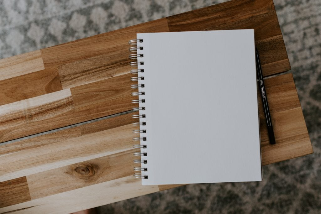 open white blank notebook sitting on a wood and grey rug background