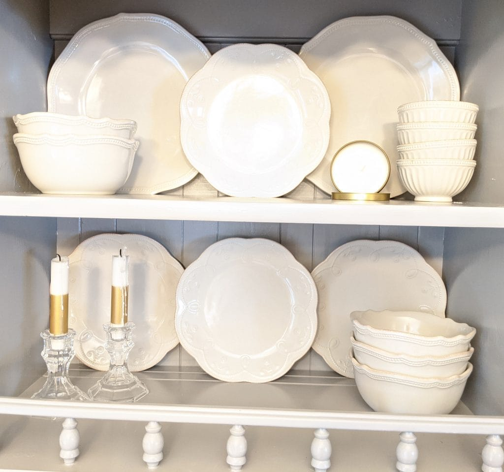 White china dishes and a white candle in a gold container and white and gold candlesticks in crystal candleholders sitting arranged on two grey shelves with a grey wood background