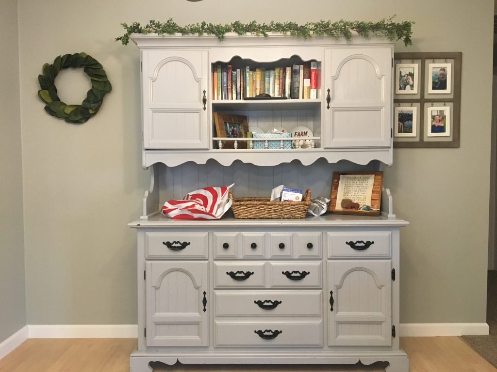 A grey dining hutch with a magnolia wreath on one side and 4 picture frames on the other. Hutch is against a grey wall and filled with books, a basket, a shopping bag and clutter