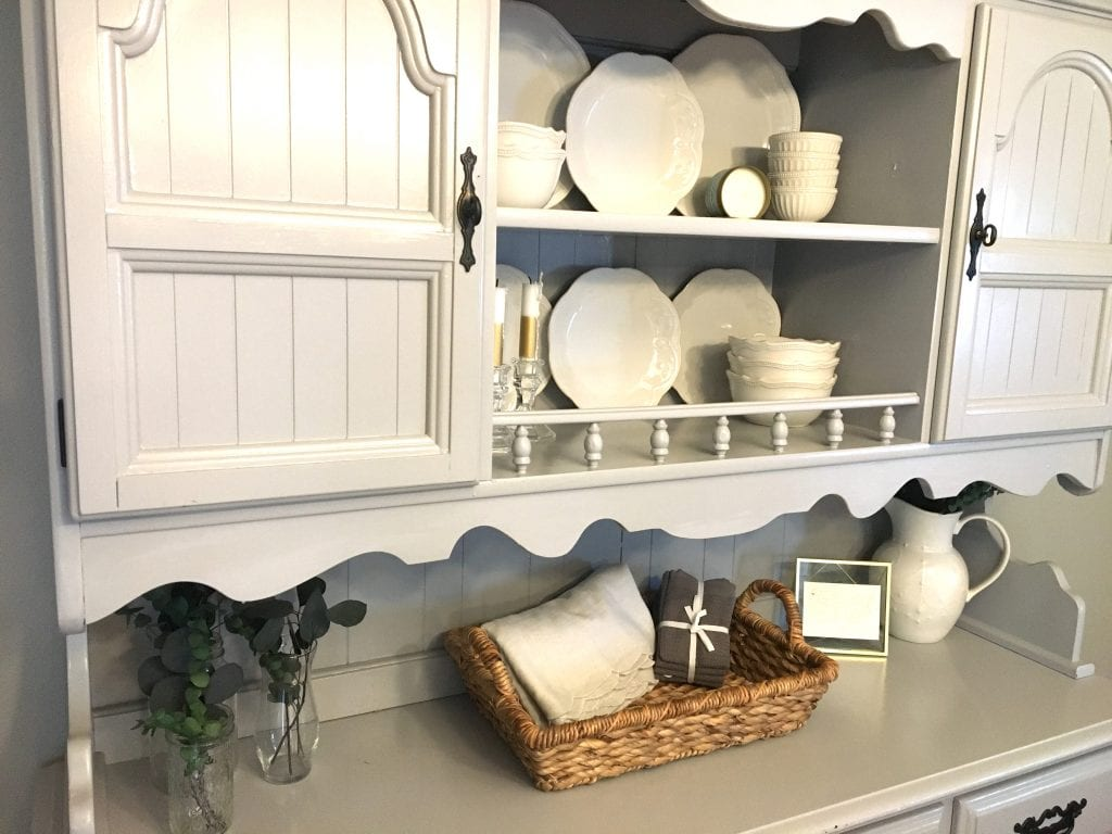 A close-up of a grey dining hutch with white china arranged on the upper two shelves and greenery in glass vases and greenery in a white pitcher, as well as a woven basket with linens in it, on the lowest shelf