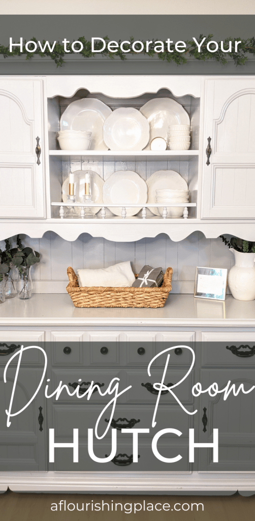 A grey dining room hutch styled with white china dishes a shallow woven brown basket, greenery in glass vases, a gold picture frame and a white china pitcher with greenery in it.