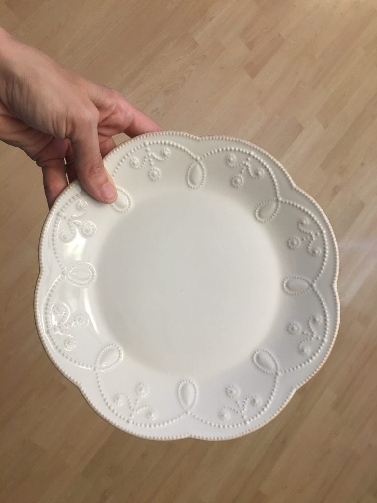 Close-up of a white china plate against a wood floor background