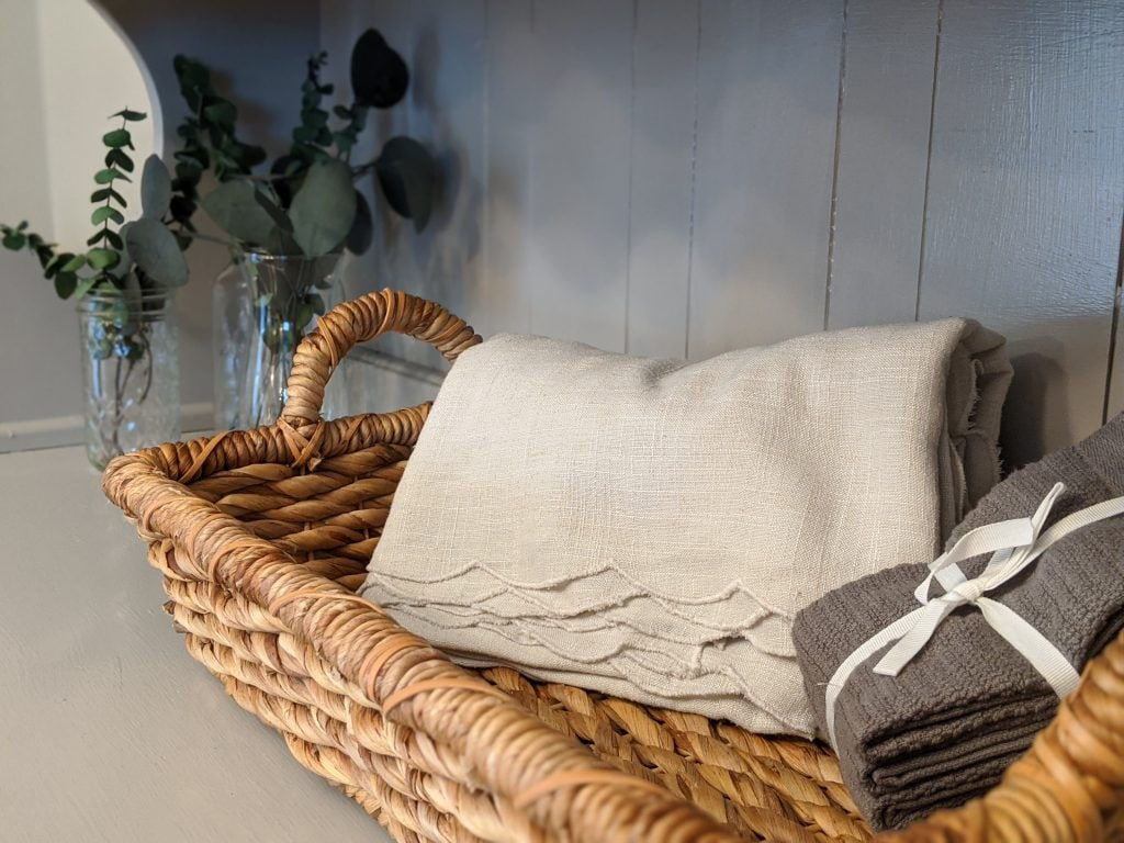 woven basket with a tan tablecloth and stack of grey washcloths sitting on a grey shelf with three glasses vases full of greenery in the background