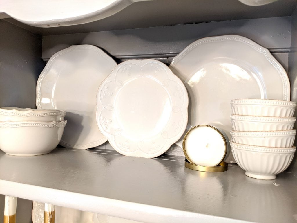 White china dishes and a white candle in a gold container sitting arranged on a grey shelf