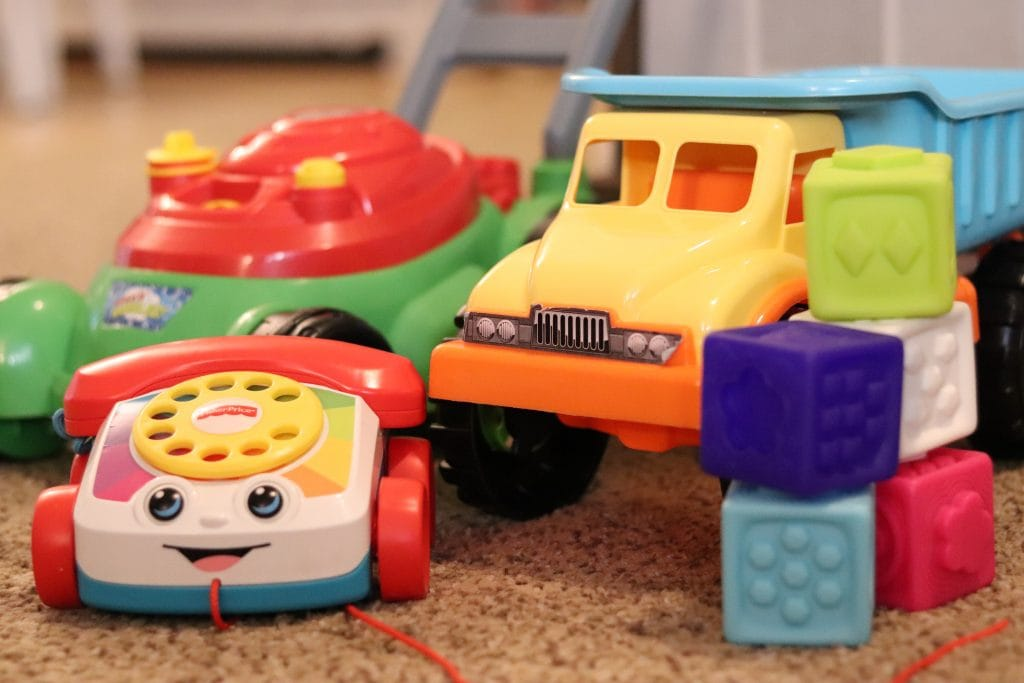 a toy lawnmower, a toy phone, a toy dump truck and five colored toy blocks all arranged together on tan carpet