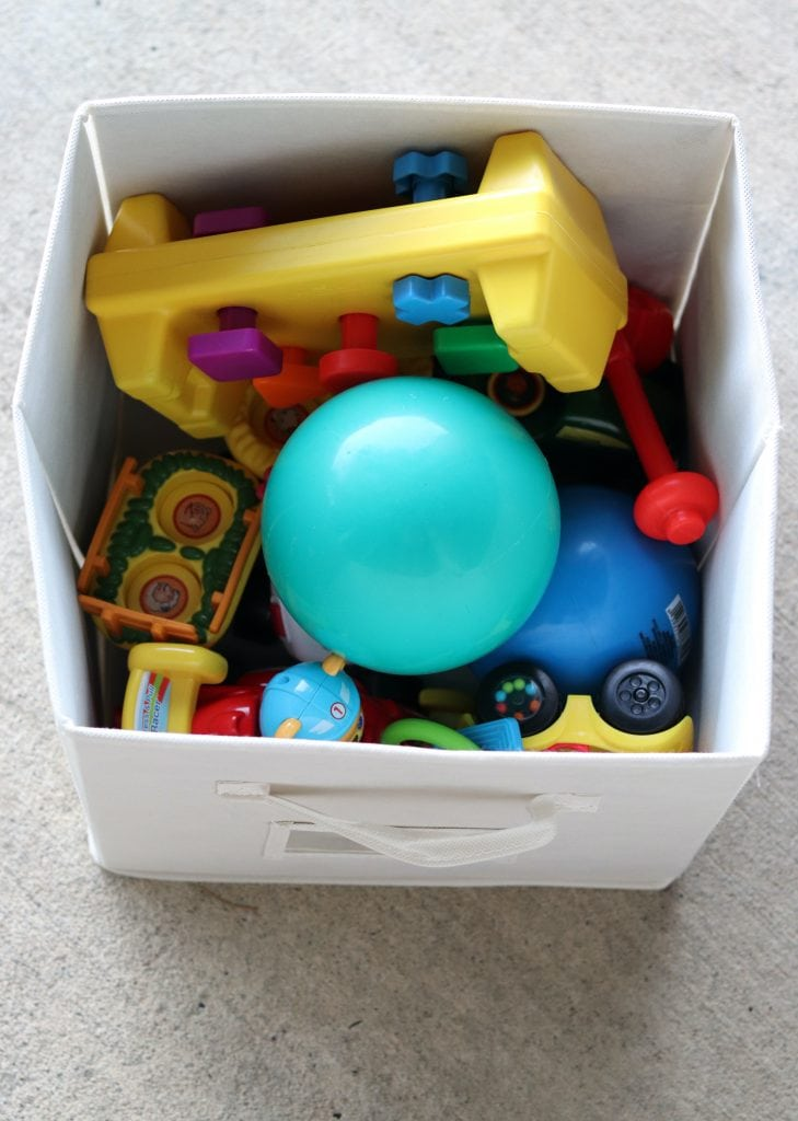 Baby toys in an ivory collapsible cube bin on a concrete background