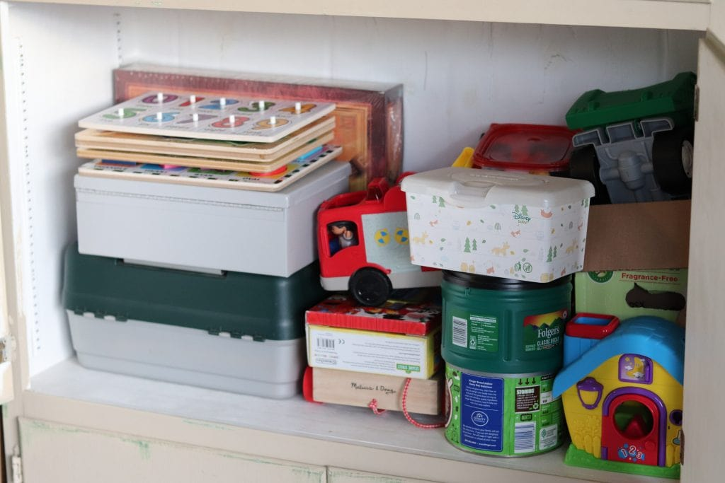 several boxes, wood kids puzzles, two green coffee cans  and various kids toys sitting on a shelf in a cupboard with the doors open