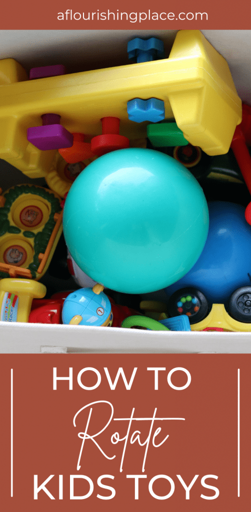 Several brightly colored baby toys including a teal rubber ball gathered in an ivory bin