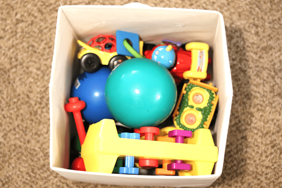 ivory bin of brightly colored baby toys agains a tan carpet backdrop