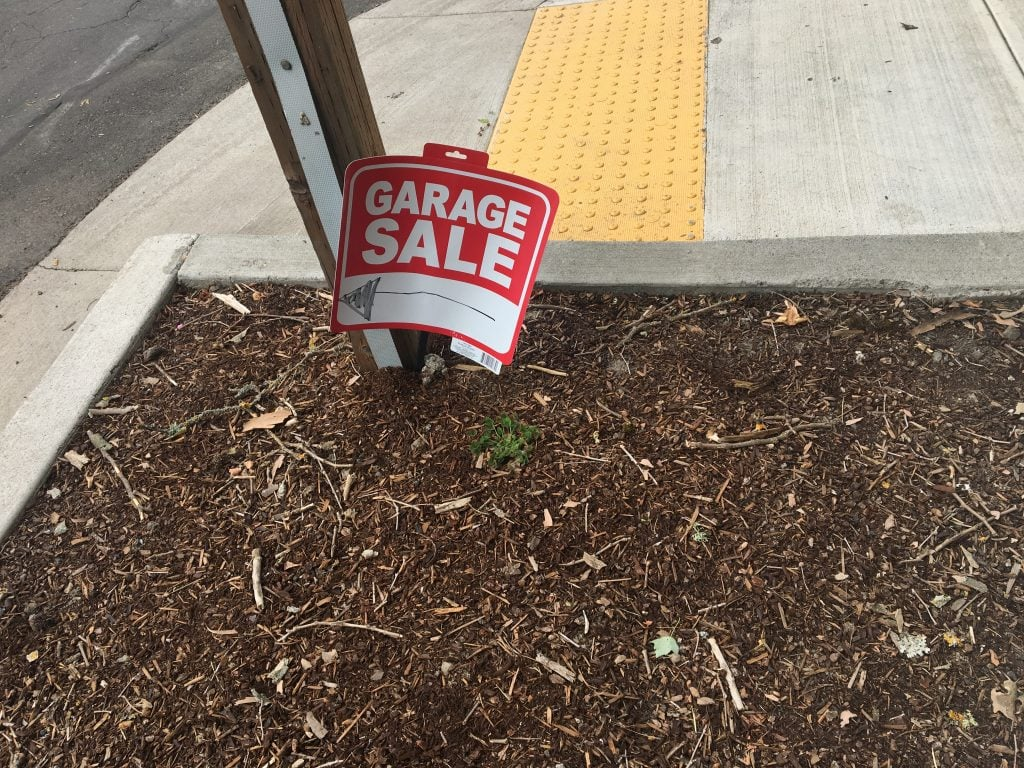 A red and white garage sale sign stuck into bark dust. Base of a stop sign and a sidewalk in the background.
