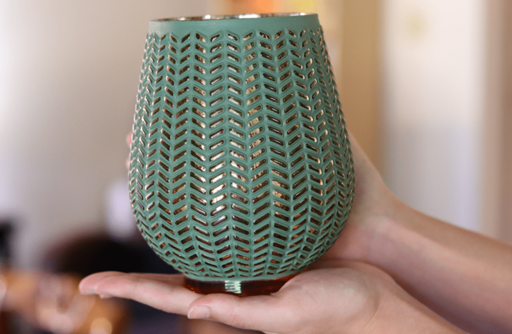 a gold and seafoam green vase being held by two hands