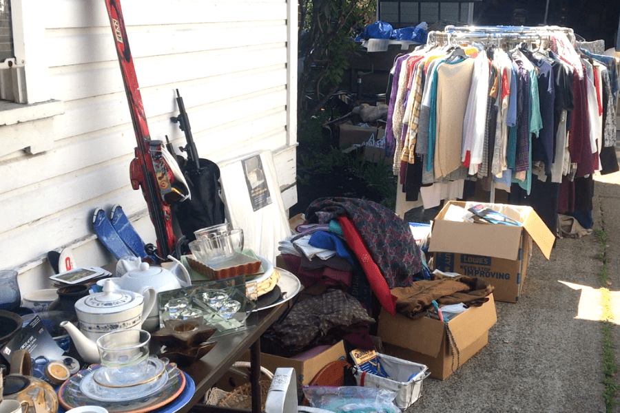 A garage sale with knickknacks and dishes laid out on a table and hanging clothes on a rack