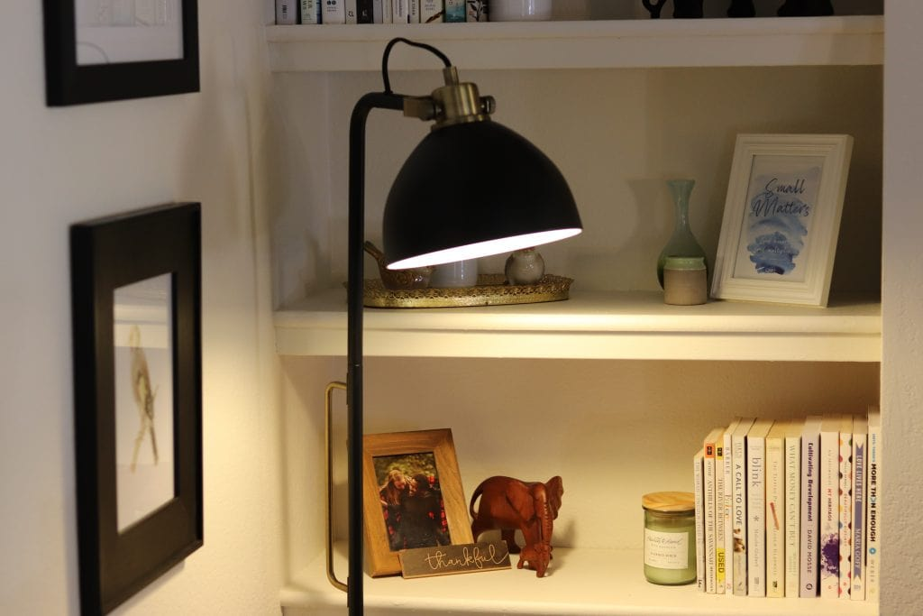 a black floor lamp shining down with two black photo frames on the wall behind and white bookshelves in the background with white books and knickknacks on it