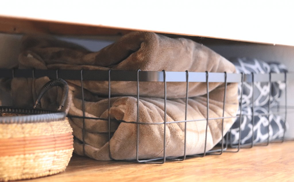 a woven basket and two wire baskets holding blankets under a white bench on a wood floor.