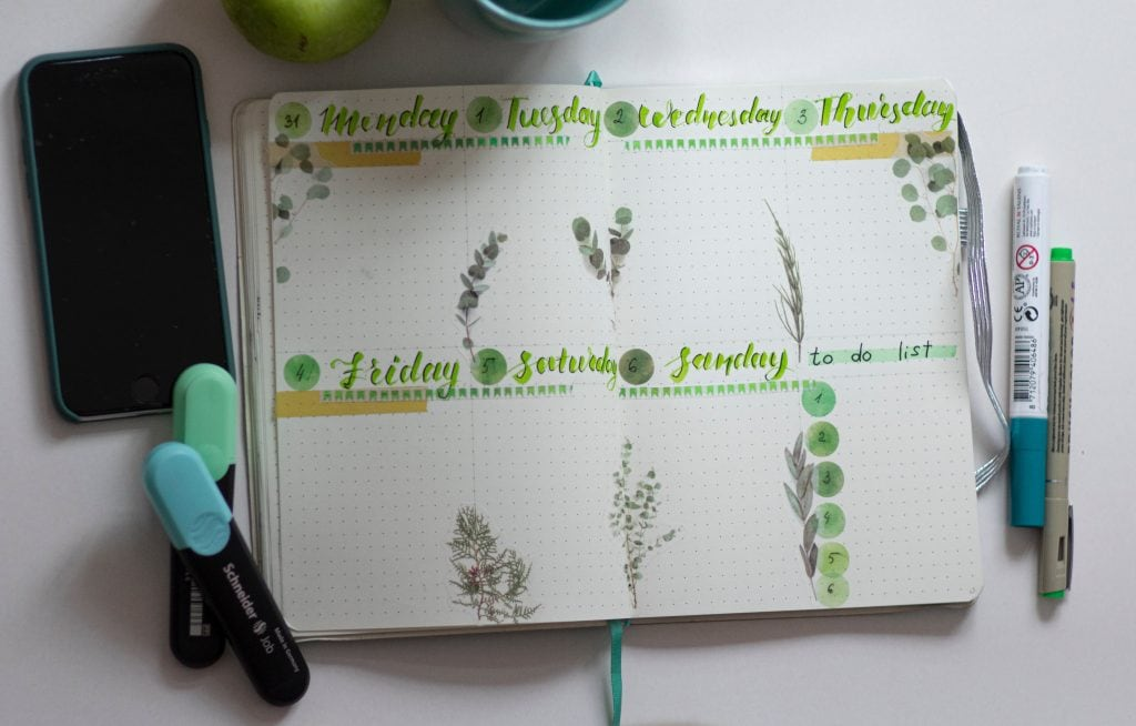an open journal showing the days of the week written out and a to-do list, with a smart phone and several pens beside it