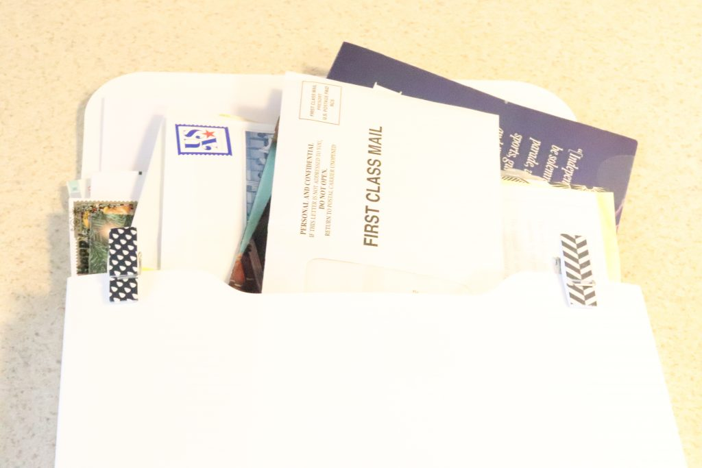 stack of mail in a white organizing pocket against a cream background