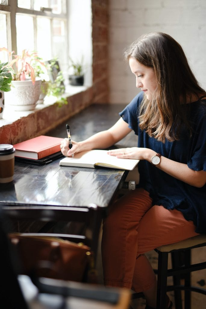 a brunette woman in a navy shirt and peach colored pants sitting at a long table writing in a notebook. A window is in front of her and a cup of coffee in a travel cup is on the table.