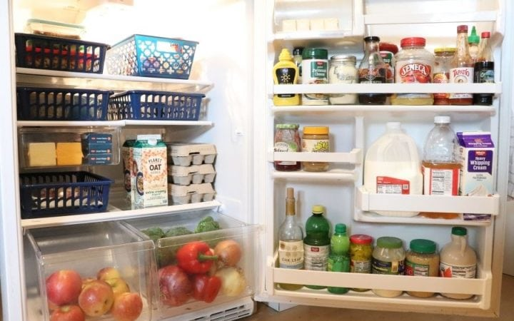 Open refrigerator filled with food arranged in navy blue baskets