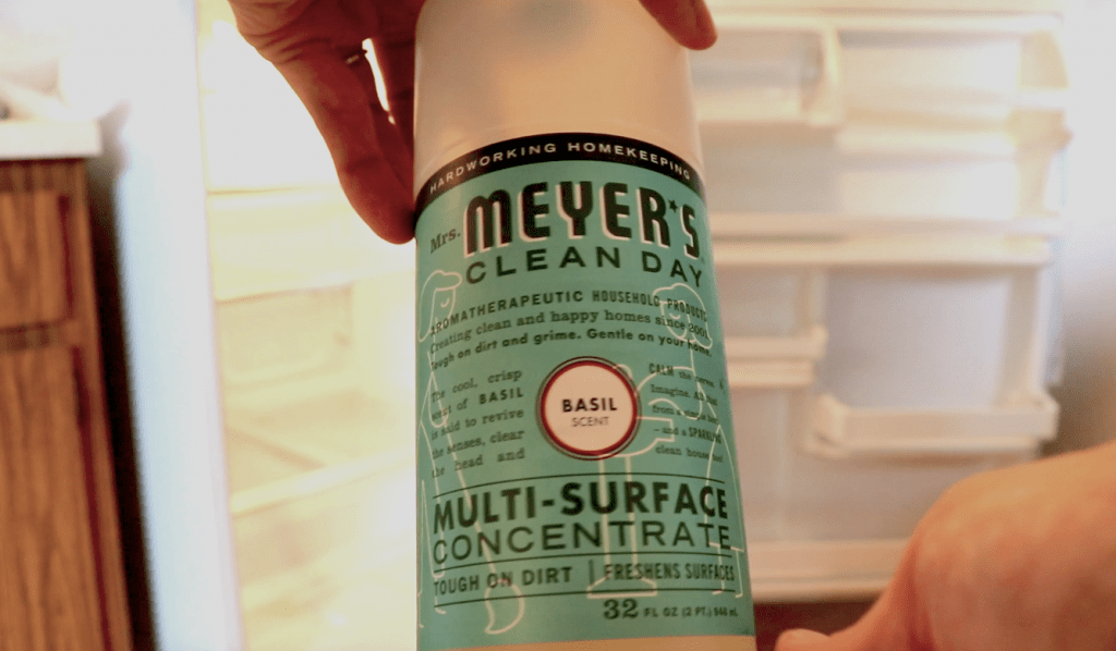 Close-up of two hands holding a bottle of Mrs. Meyer's Multi-Purpose Spray