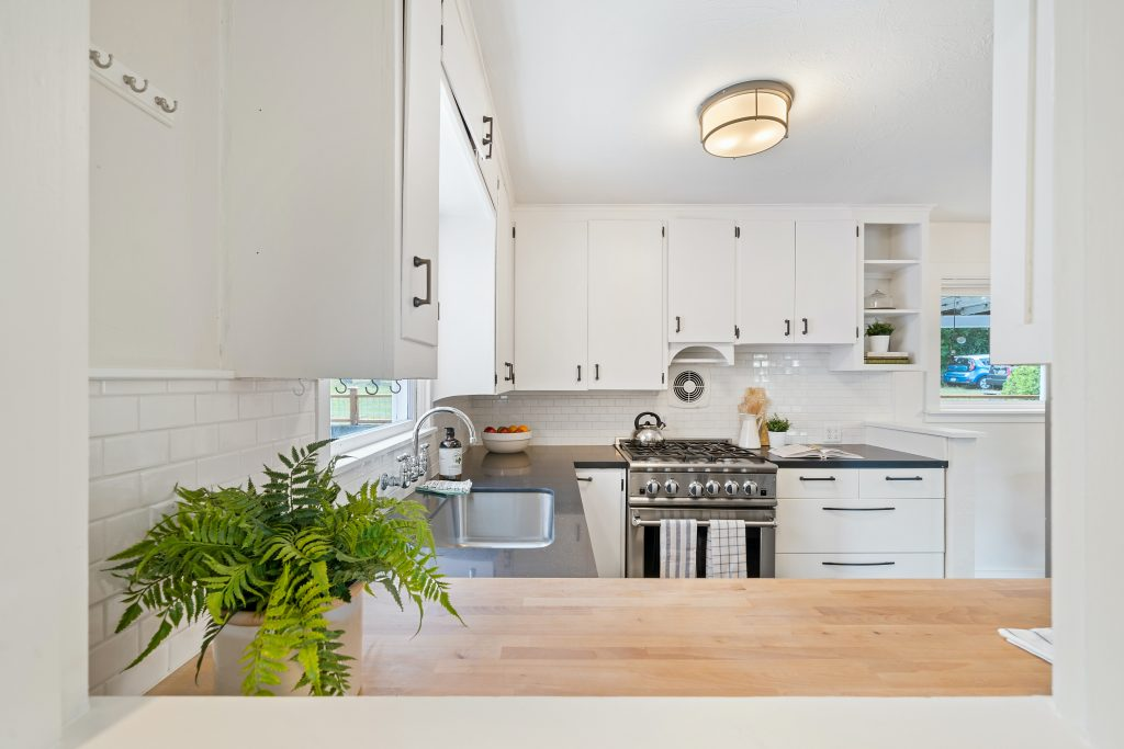 A kitchen with white cabinets, a stainless steel stove and butcher block countertops with a fern in a pot sitting on top.