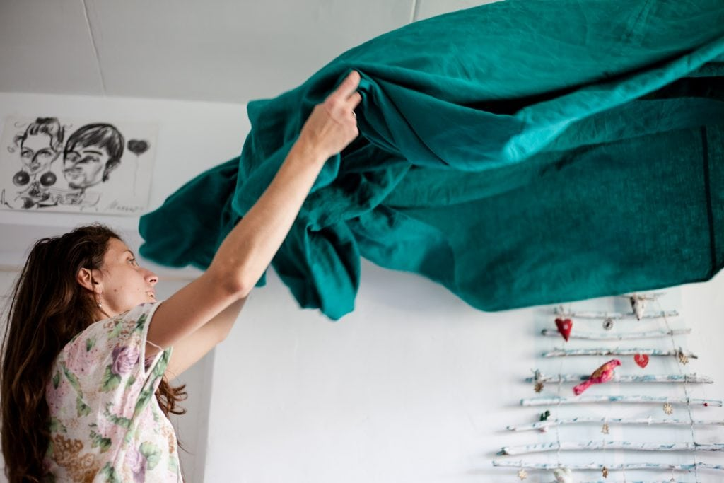 A brunette woman lifting up and spreading a turquoise sheet out to put on a bed.