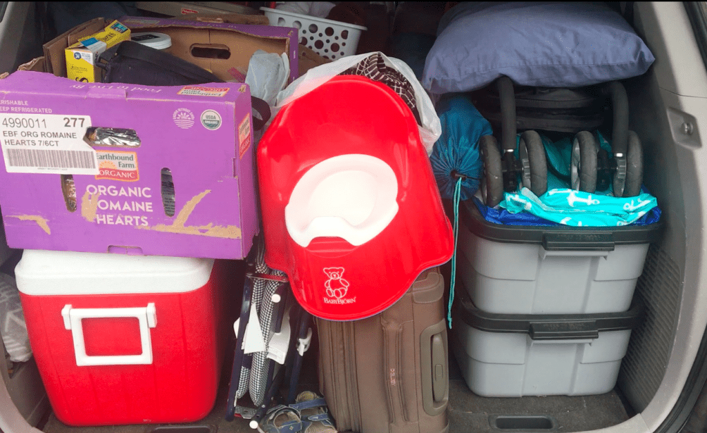 back of a van filled with a red cooler, a purple box, a red potty chair, a couple of grey rubbermaid tubs, a pillow and a stroller