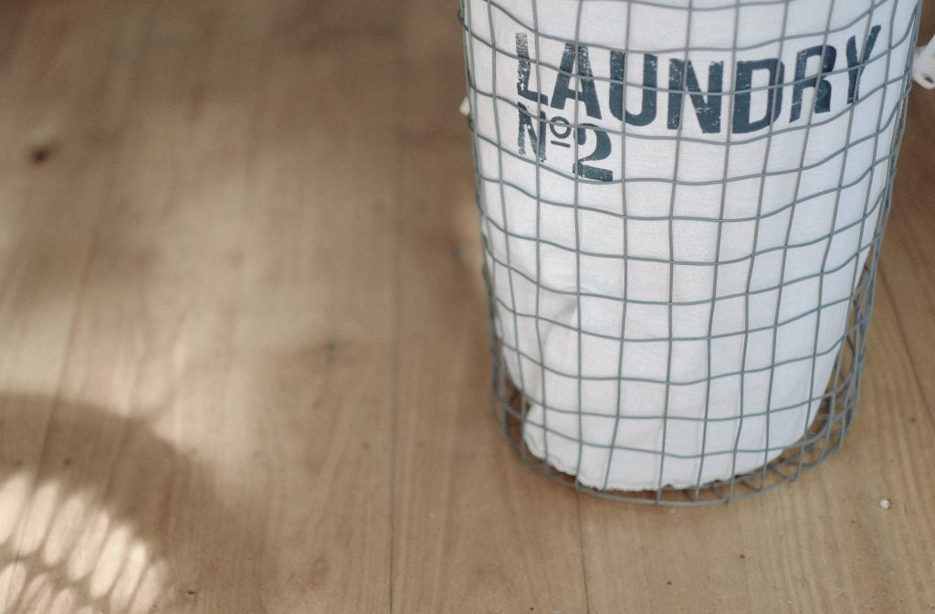"""a wire laundry basket with a tan liner that says """"Laundry No. 2"""" with a wood floor background"""