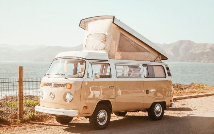 a tan camper van parked on a road with the ocean in the background