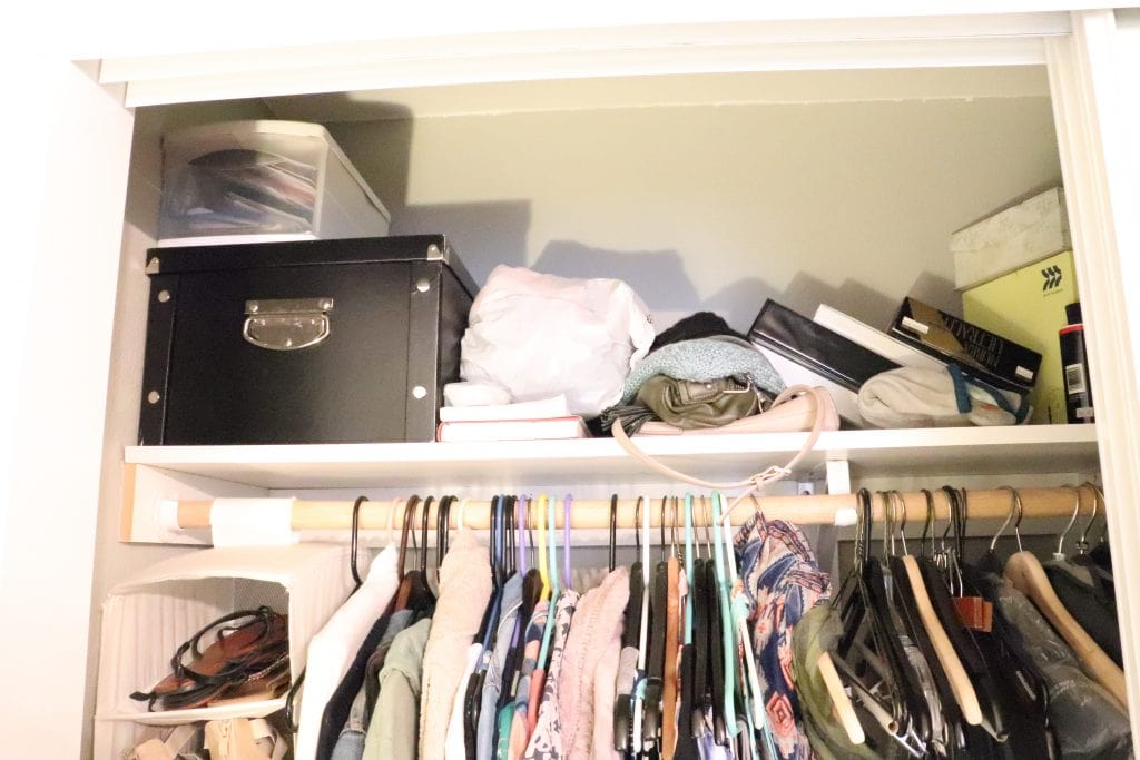Open closet with a hanging shoe organizer, clothes hung up, and a top shelf with a black box, a plastic box and several various notebooks and clutter