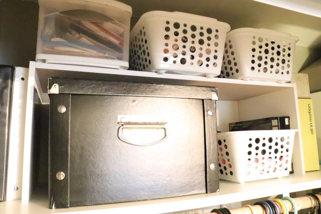Top shelf of a closet with a black box and several white plastic bins organized on two shelves