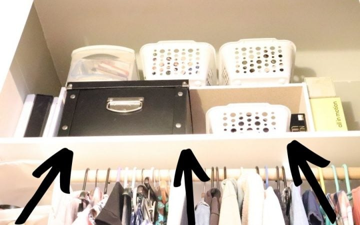 Top shelf of a closet with a black box and white plastic bins on two different shelves, and black arrows pointing up to it.