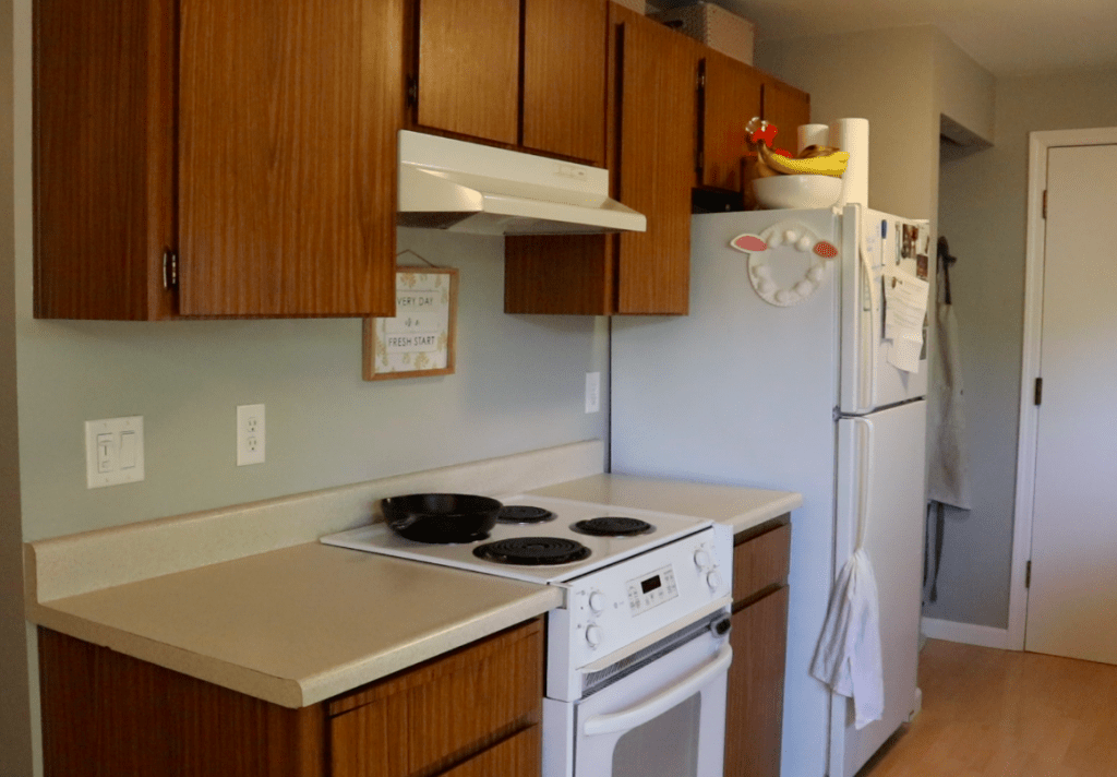 1970's wood kitchen cabinets with a white range, white range hood, white refrigerator and neutral countertops