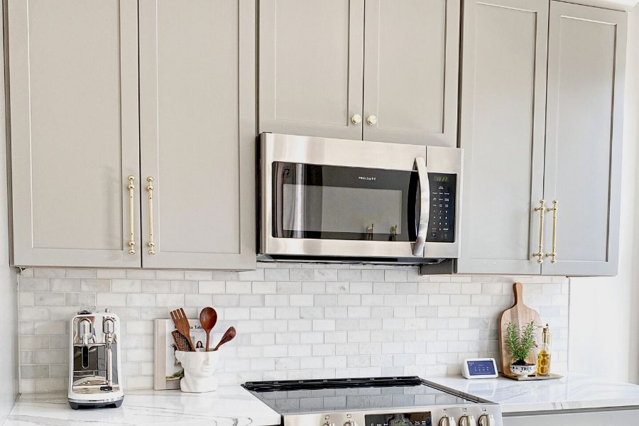 A bank of grey shaker front cabinets with a stainless steel wall mount microwave