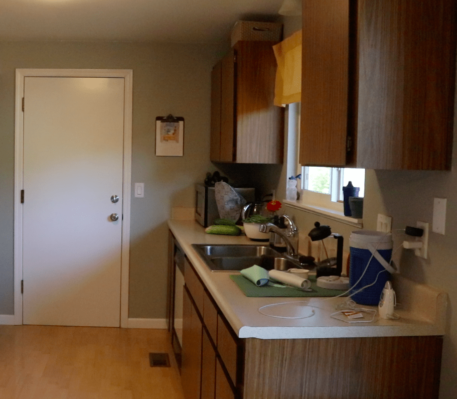 One wall of a kitchen with 1970's flat front wood kitchen cabinets, neutral counterops with dishes, a stainless steel sink and a stainless steel microwave and a yellow valance over the window. White door on a gray painted wall in the background.