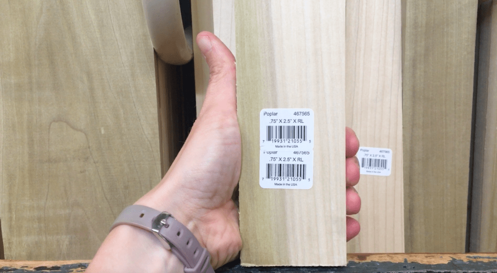 A hand holding a piece of poplar trim board, with more trim boards in the background