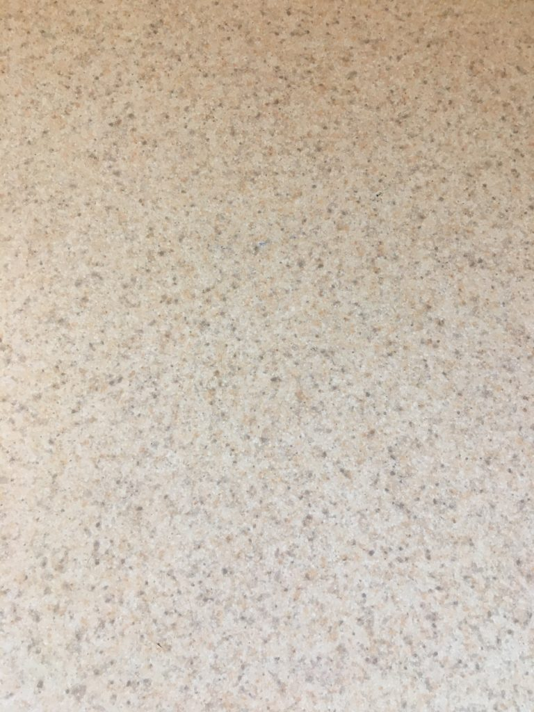 Close-up of a neutral laminate countertop incorporating grey, tan, and cream flecks