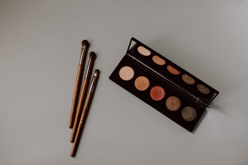 three makeup brushes and a palette of makeup against a white background