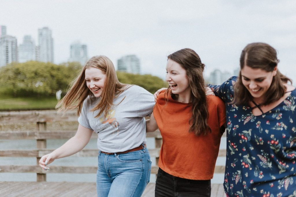 three women walking along with their arms across their shoulders laughing together with a background of some greenery and a city skyline in the far distance