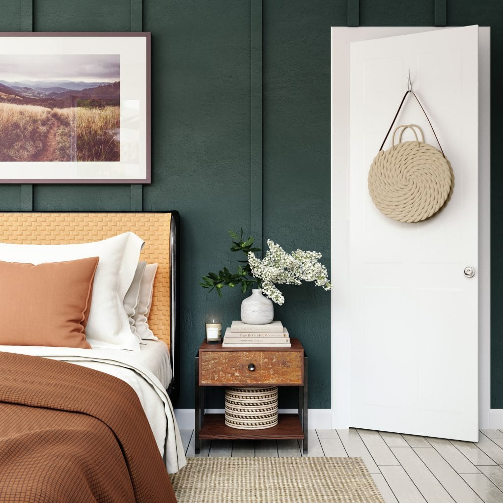 Hunter green board and batten wall background with a white door on the right, a wood nightstand in the middle and a made bed on the left with a tan headboard, a large landscape painting above it and brown blanket spread over it